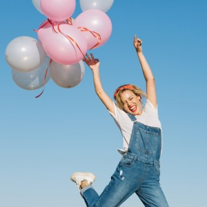 cheerful-woman-releasing-balloons_23-2147699198